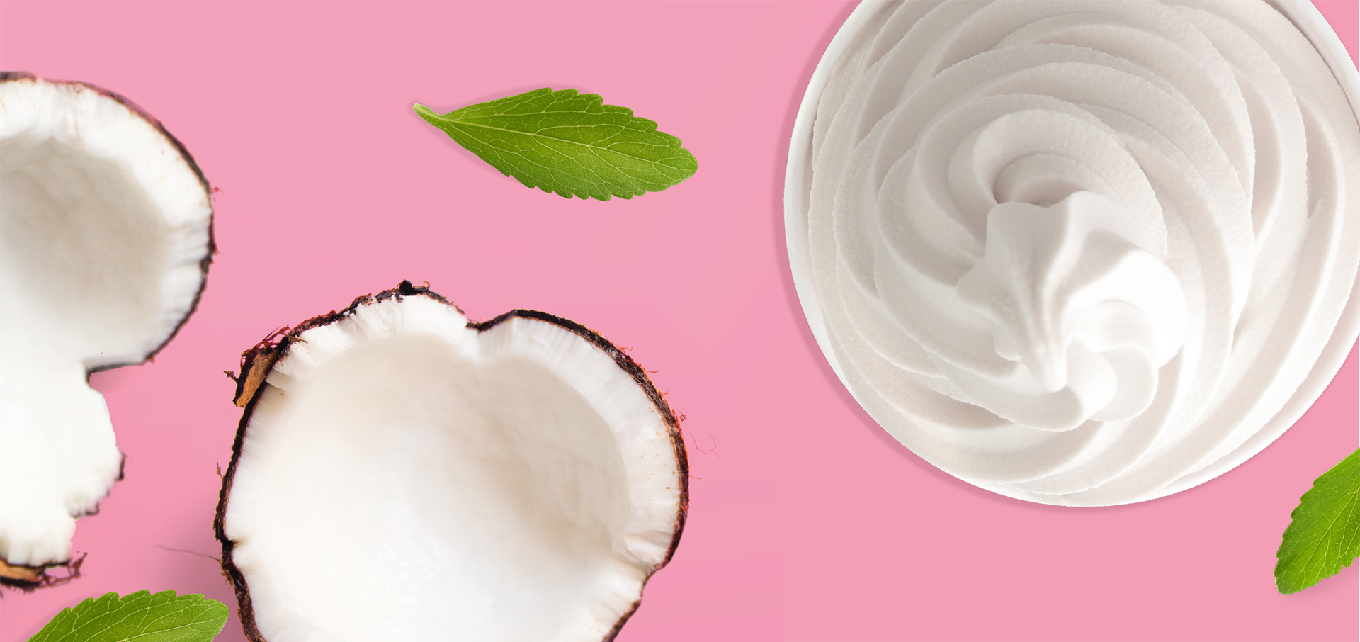 A coconut split in half alongside a cup of yogurt