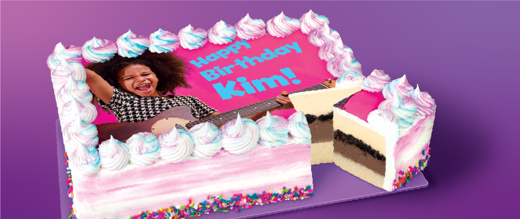 A birthday cake with a photo of a girl on top and text