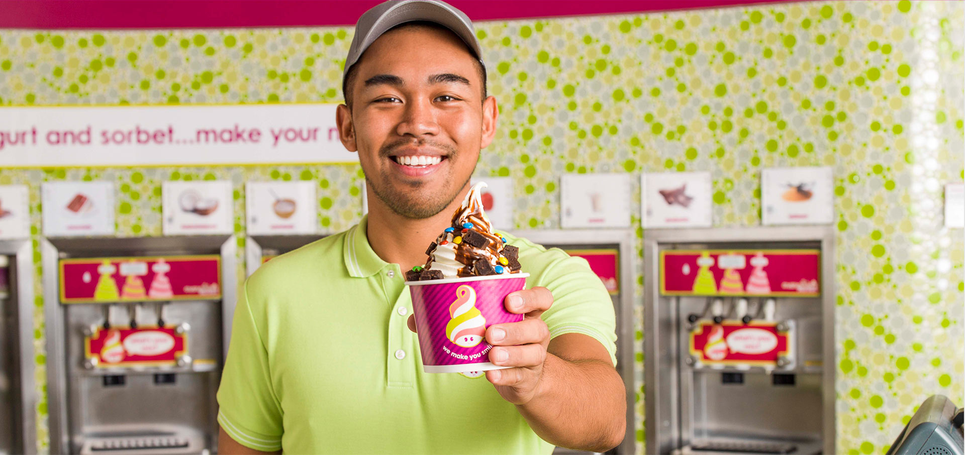 A Menchie's employee preparing toppings
