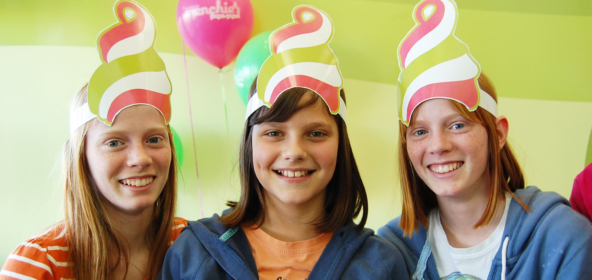 Three girls wearing Menchie's party hats