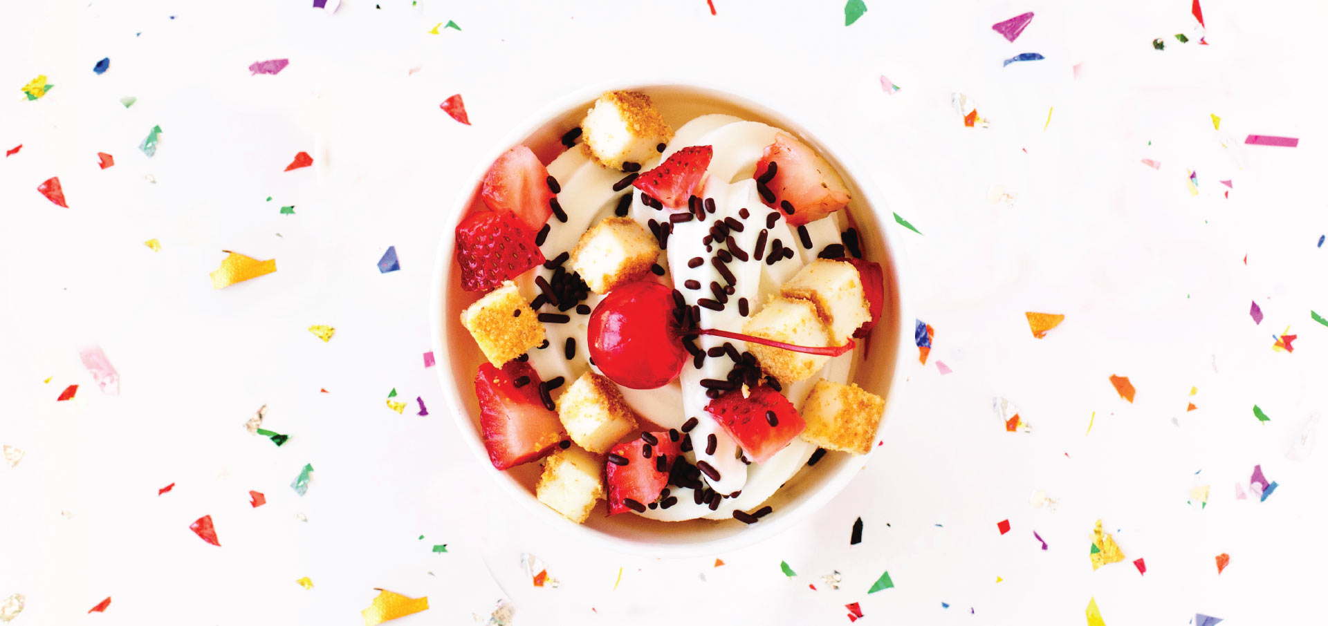 A bowl viewed from the top with fresh fruit, frozen yogurt, and chocolate sprinkles and a background of confetti on white