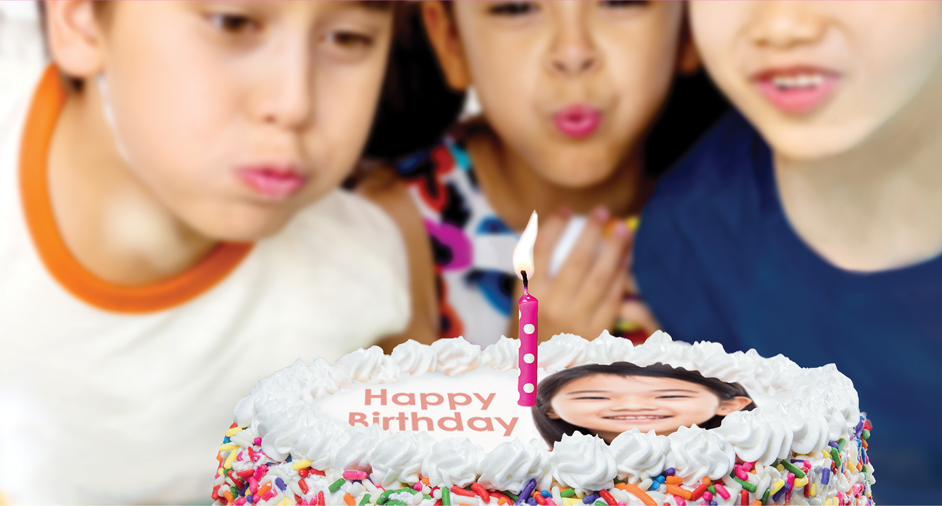 Three children blowing out a birthday candle on top of a Menchie's frozen yogurt cake